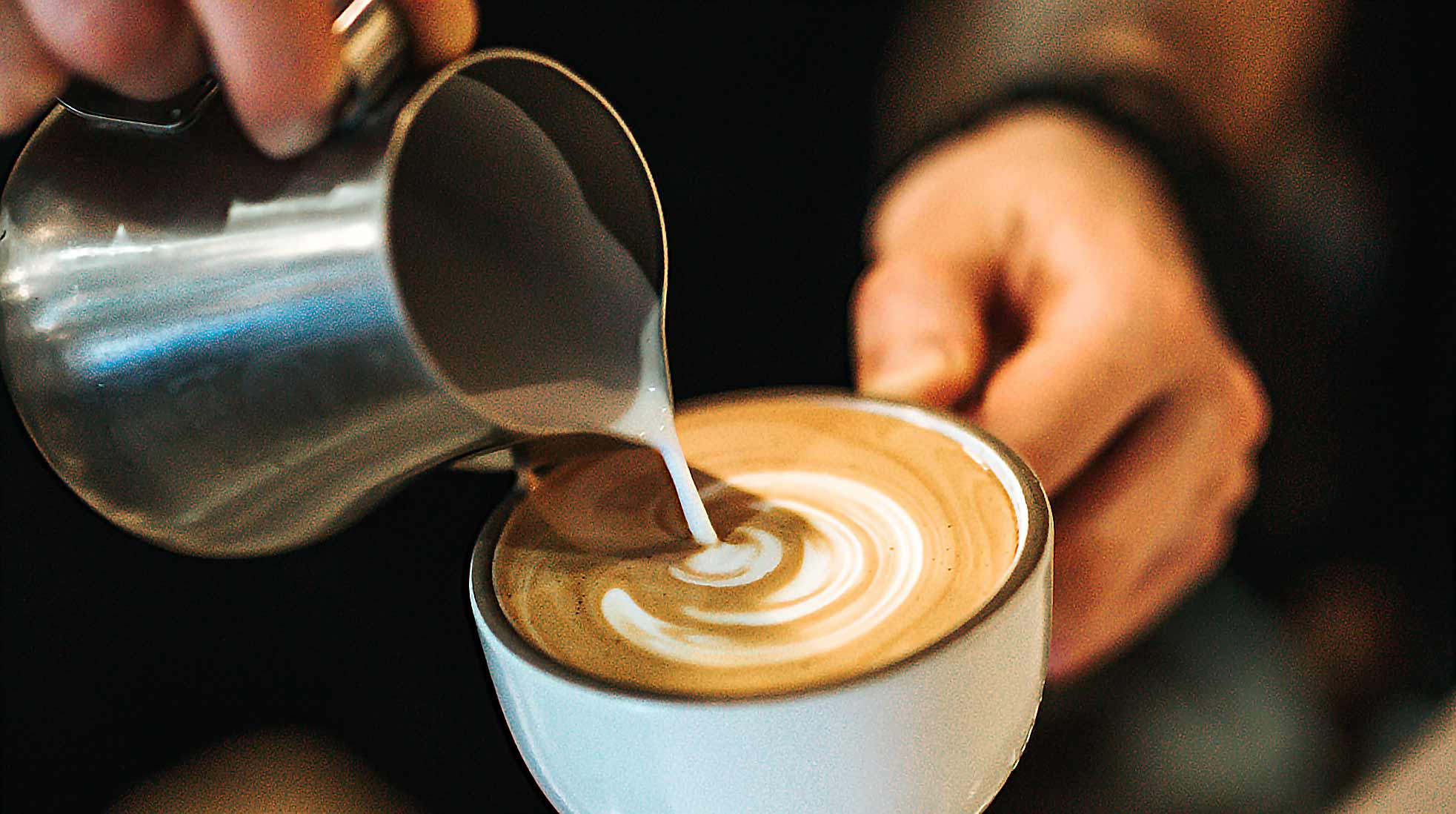 A cappuccino being poured by a barista at a coffee shop